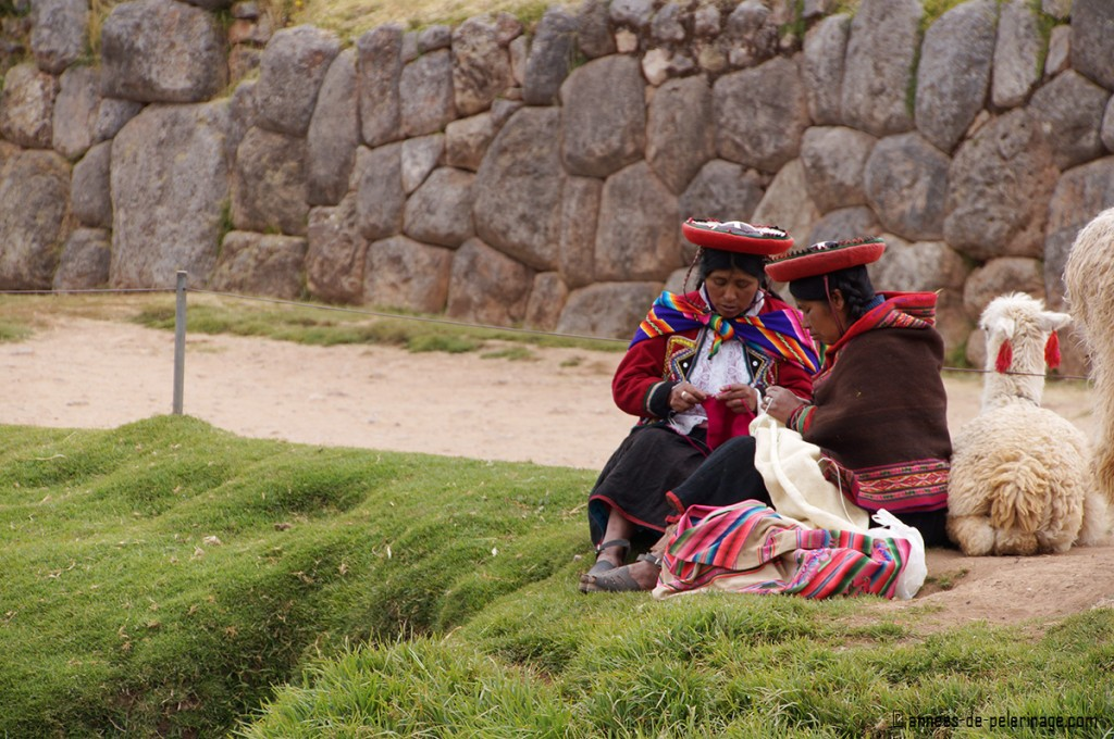 Two local womean knitting at the foot of the ruins of Sacsayhuamán in Cusco, Peru