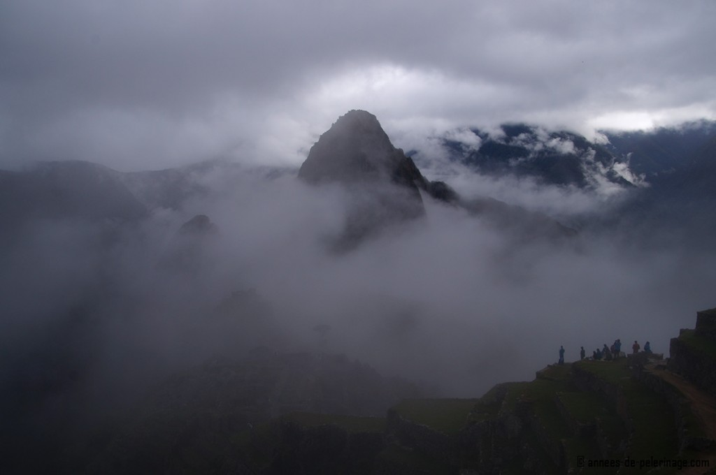 Waiting for the sun rise in machu picchu with heavy fog disturbing the view