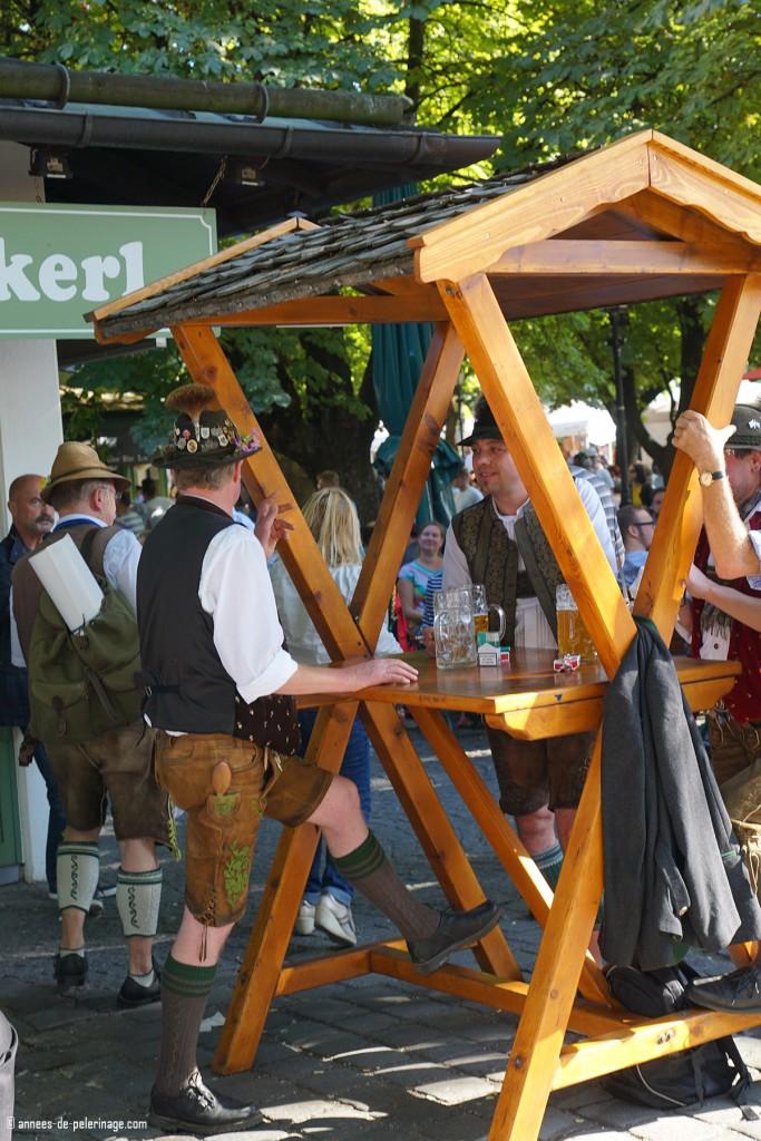 Locals drinking beer in the beergarden on Viktualienmarkt in Munich wearing traditional bavarian cloths
