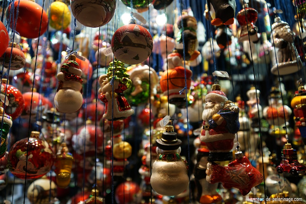 colorful christmas tree decorations hanging on lines inside a booth on the Christmas market in Munich