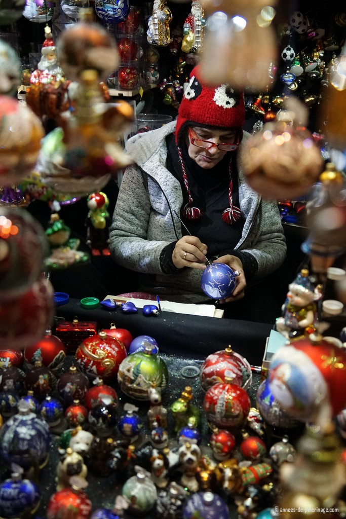 A woman painting christmas tree balls on the Christmas market in Munich
