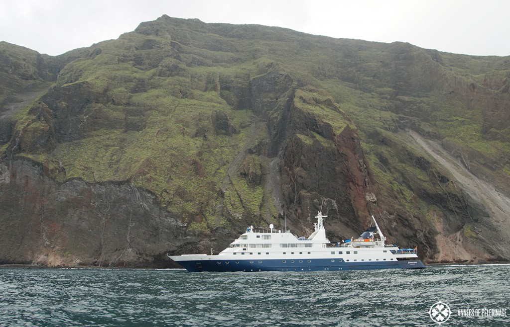 The Celebrity Xpedition Galapagos luxury cruise ship in front massive volanic rock formations