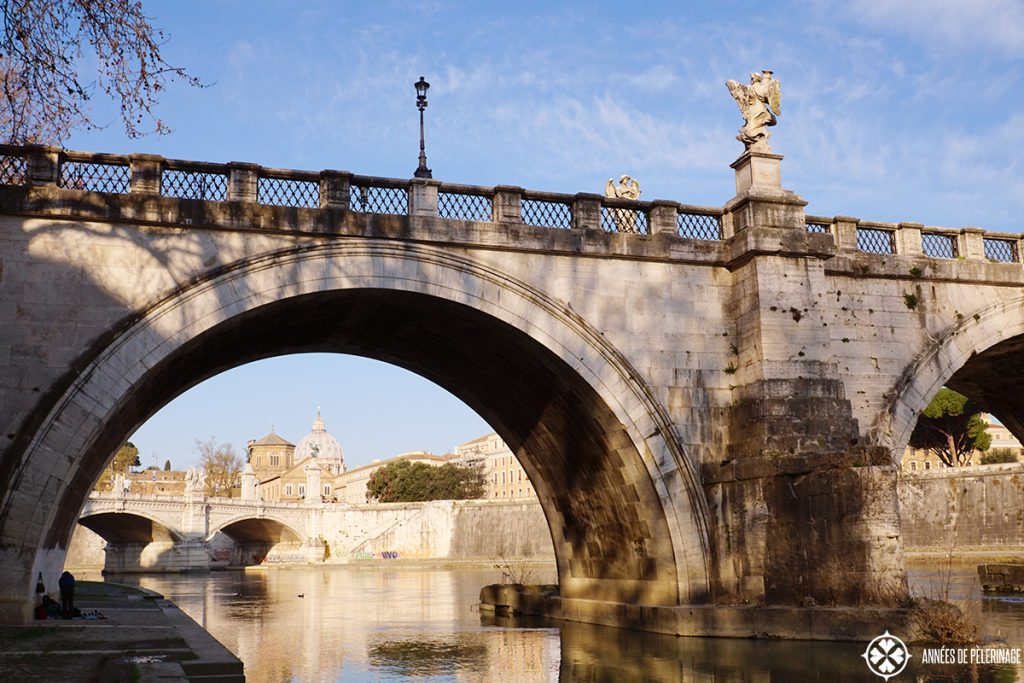 The banks of the Tibe river seen through the Angel Bridge and the Vatican in the background