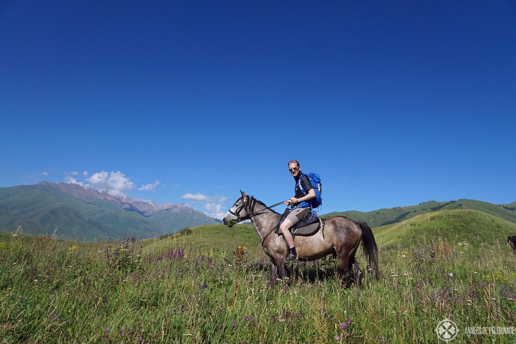 Horse riding in Kyrgyzstan over a high mountain mass among a beautiful blooming meadow.