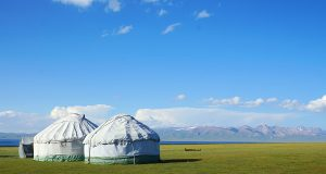 Son-kul lake with two yurts standing near its shore in Kyrgyzstan, just one of many free things to do in Kyrgyzstan, Central Asia