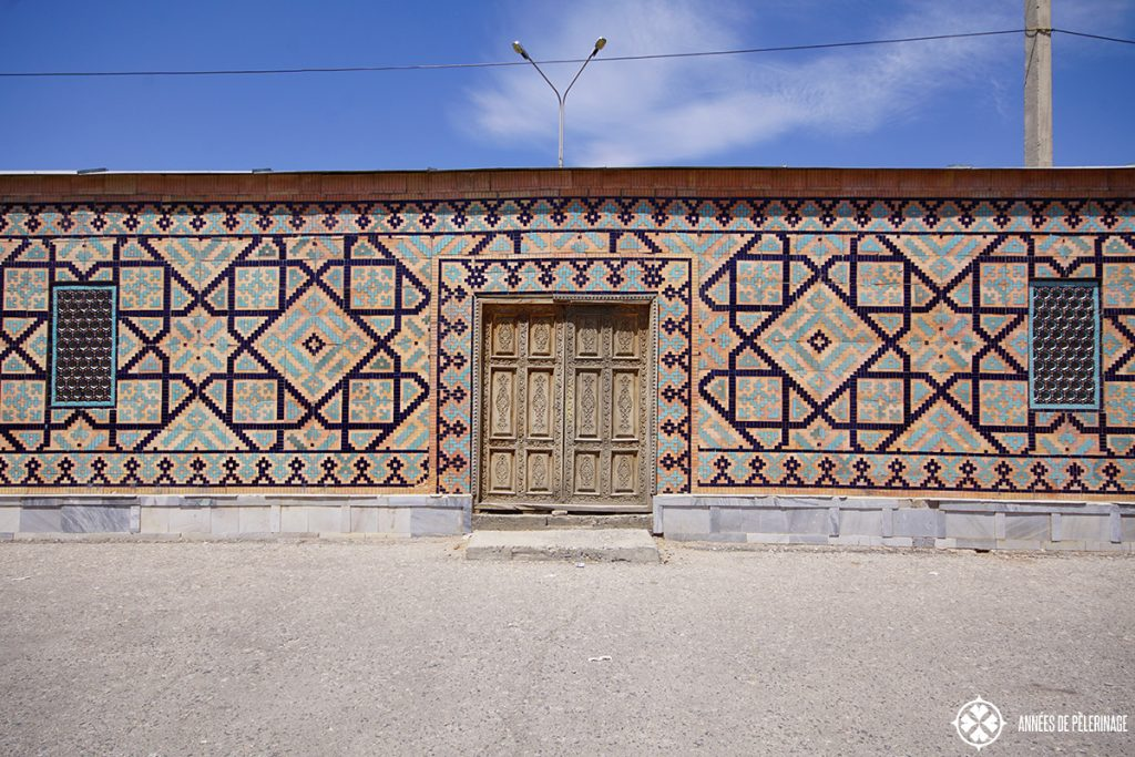 A tiled wall in Samarkand, Uzbekistan with a simple wooden door
