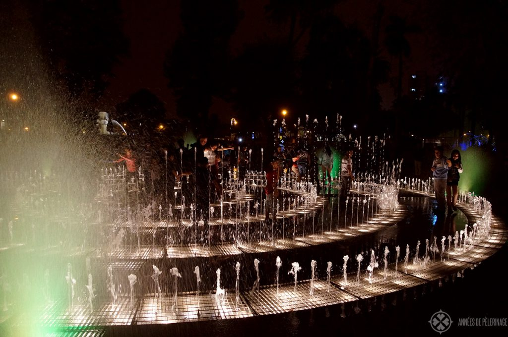 Children playing among the fountains at the water park in Lima Peru