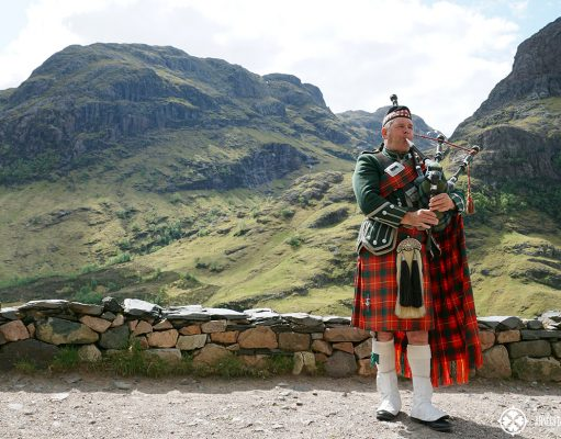 Glen Coe in Scotland and man playing bag pipes