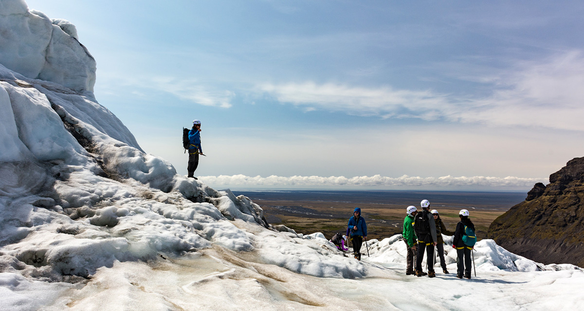 A group of travelers on a glacier hike in iceland, all wearing glacier hiking boots and crampons