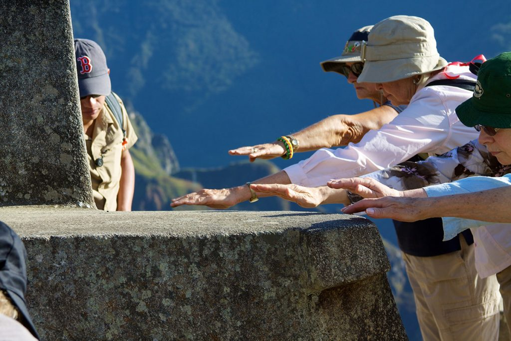 Tourists feeling for the energy emanating from the Intihuatana stone in Machu Picchu