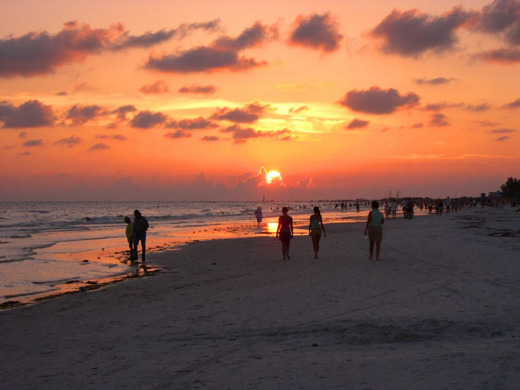 crowds walking along SIesta Beach, florida at sunset