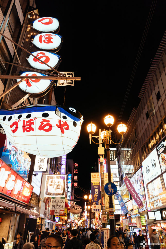 The shopping streets of the Dotombori district in Osaka at night with many lanterns and billboards