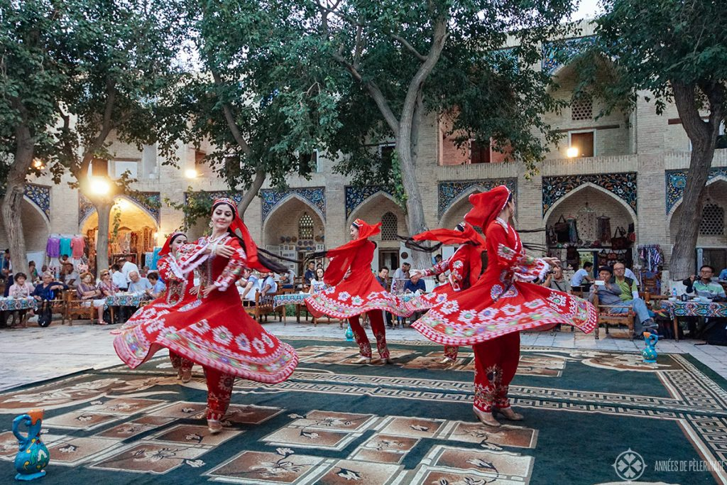 dancers in traditional red dresses at a show in Bukhra, Uzbekistan