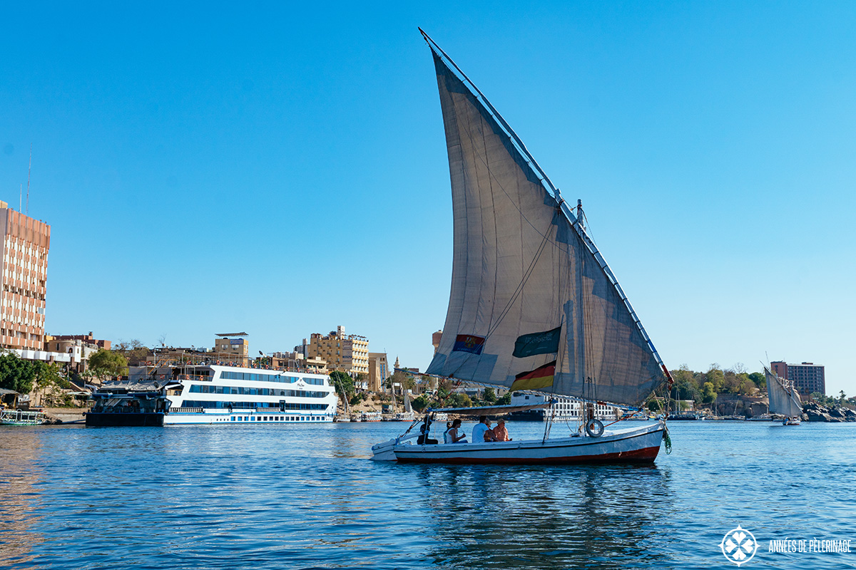 The oberoi Zahra luxury nile cruise ship with a traditional Felucca in Aswan, Egypt