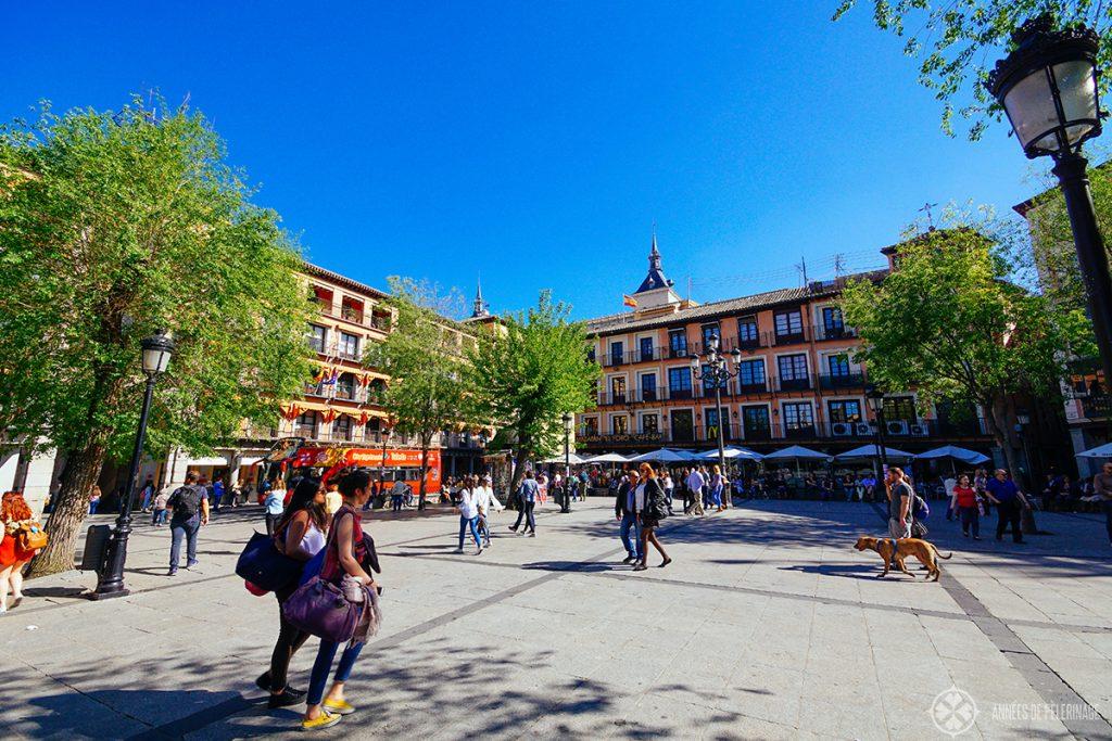 pedestrians strolling along the central Plaza de Zocodover in Toledo, Spain