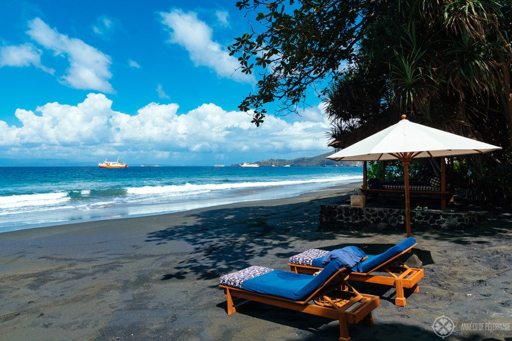 A traditional bale hut and sun loungers at the private beach of the Amankila Beach Club in East Bali