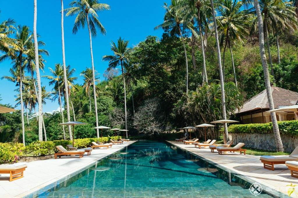 The big pool at the beach club of the Amankila luxury hotel with big palm trees offering shade