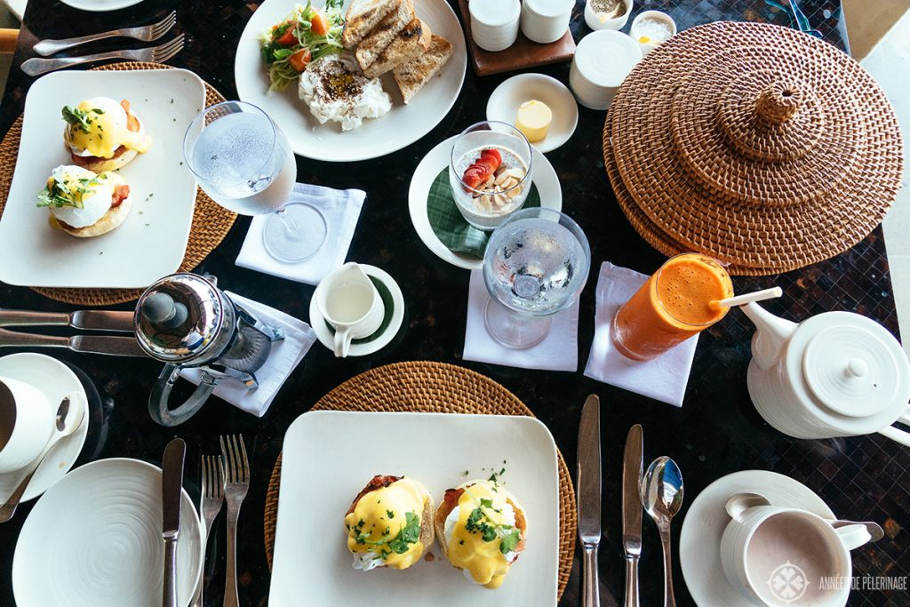 A breakfast table at the Amankila luxury hotel with fresh juice, eggs and bread basket