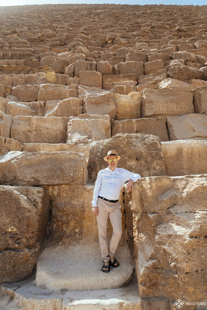 Me standing at the base of the Great Pyramid of Khufu - you can't climb them but that doesn't mean you can't get a great picture when visiting the pyramids in Egypt