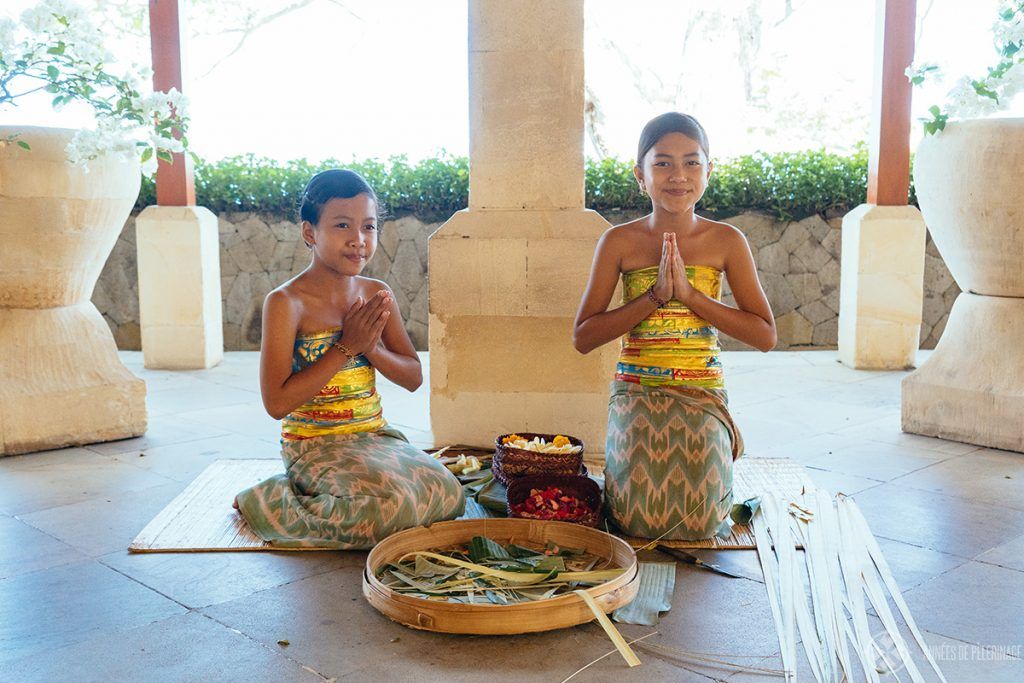Girls preparing traditional Hindu offerings in the Lobby of the Amankila luxury hotel