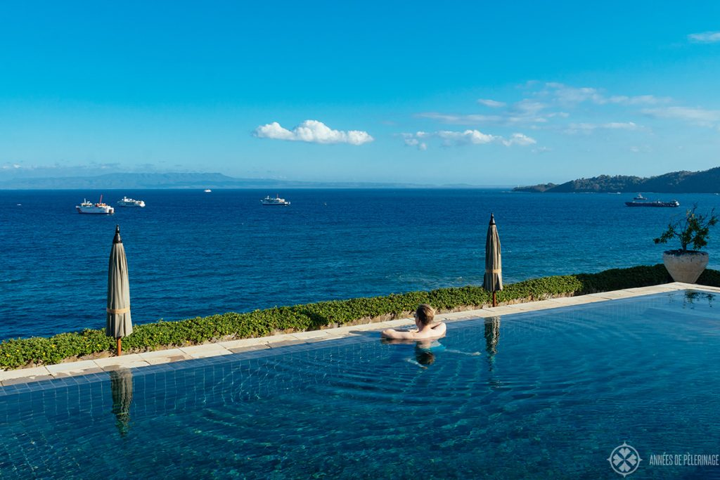 lounging in the infinity pool of the amankila luxury resort in East Bali