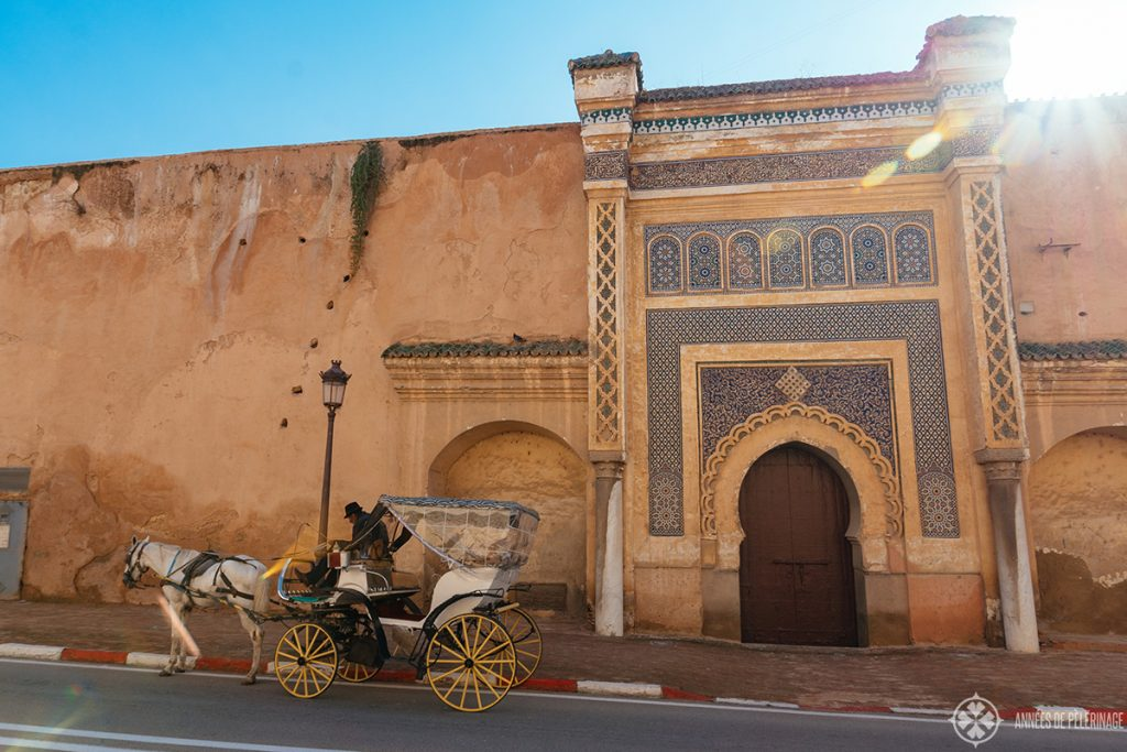A carriage driving along the old palace walls in Meknes, Morocco