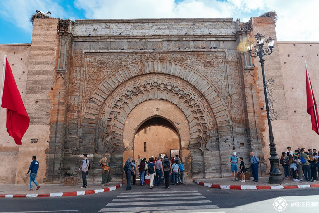 A crowd of tourists standing in front of one of the old gates into Marrakesh