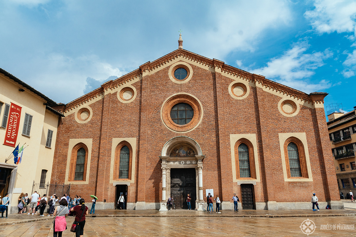 The entrance of the Last Supper Museum is on the left of the Church (where the flags are hanging down) of Santa Maria delle Grazie in Milan, Italy
