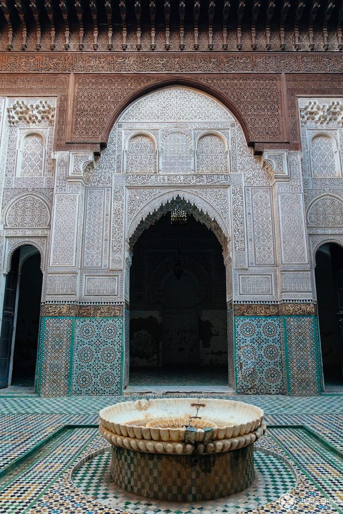 The inner courtyard of the Bou Inania Madrasa with a fountain for ritual washing before the pray. A must-see in Meknes, Morocco