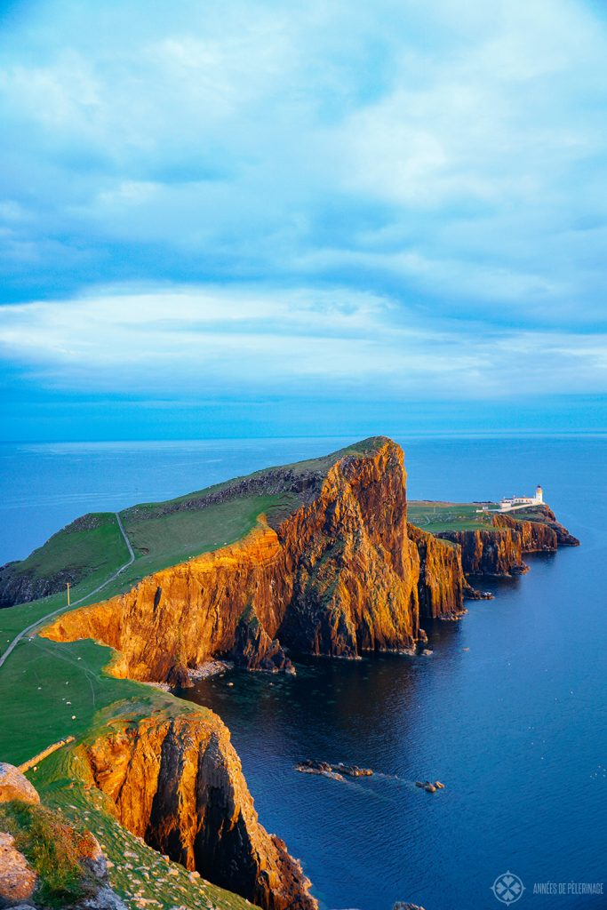 An epic sunset mood at the Neist Point Lighthouse with deep orange cliffs on the Isle of Syke, Scotland