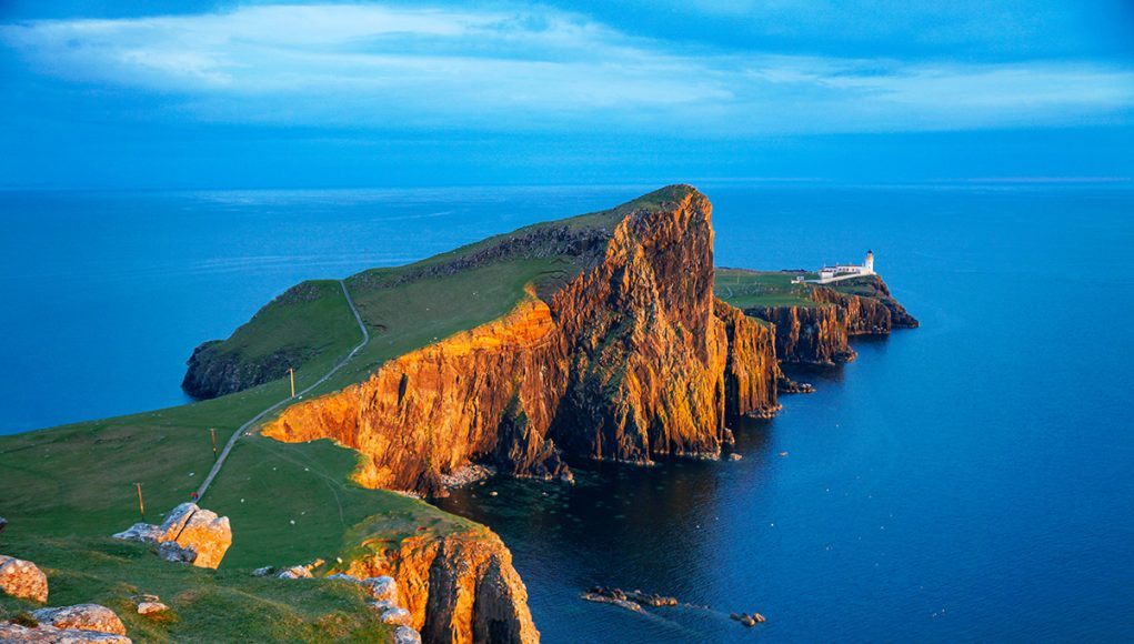 Sunset at the Neist Point Lighthouse with deep red cliffs on the Isle of Syke, Scotland