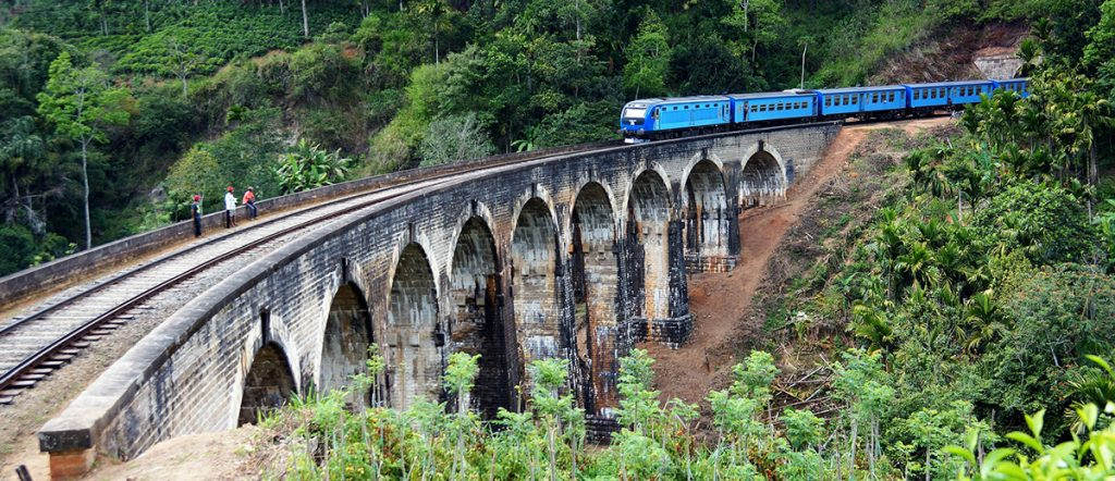 Blue train driving across Nine Arch Bridge near Ella - a tourist's favorite and a must on any sri lanka itinerary