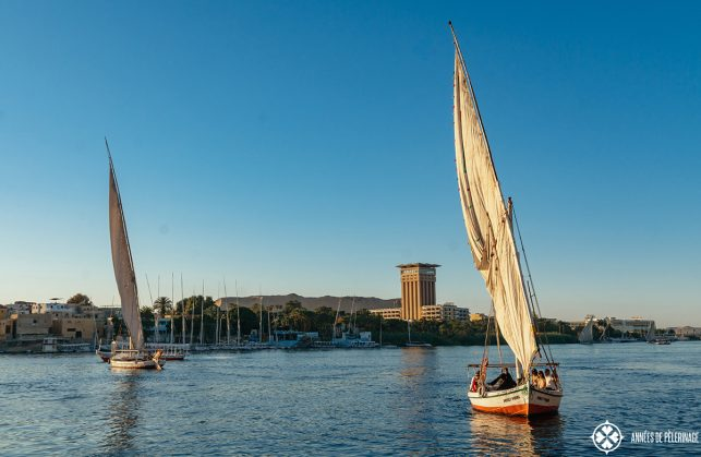 A traditional feluca with the observation tower of the Mövenpick Resort Aswan in the background