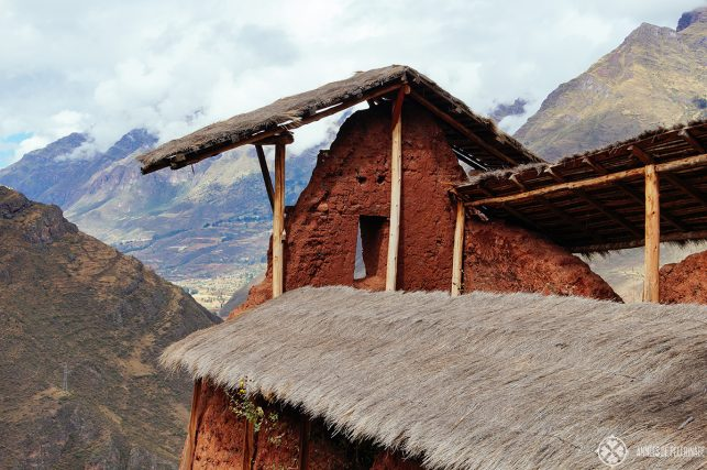Tatched roofs protecting the red adobe walls of the Kinchiraqay  in Pisac Peru