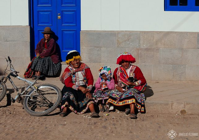 Locals in traditional andean clothing sitting on the sidewalk in Pisac's old town
