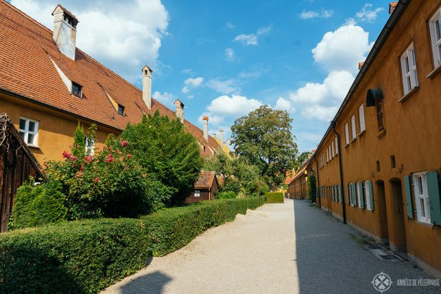 An alley inside the Fuggerei with beautiful little back gardens - one of the best places to visit in Augsburg