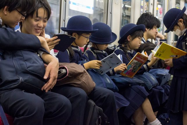 A group of japanese school children with books on the subway