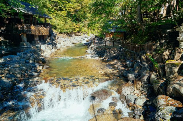 View along the mountain river with the outdoor pools of Takaragawa onsen on each side