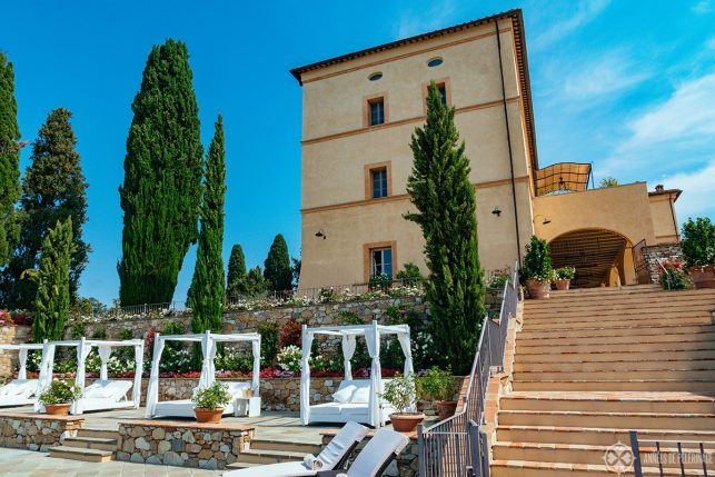 The champagne cabans at the pool with the main building of the Belmond Castello di Casole in the background