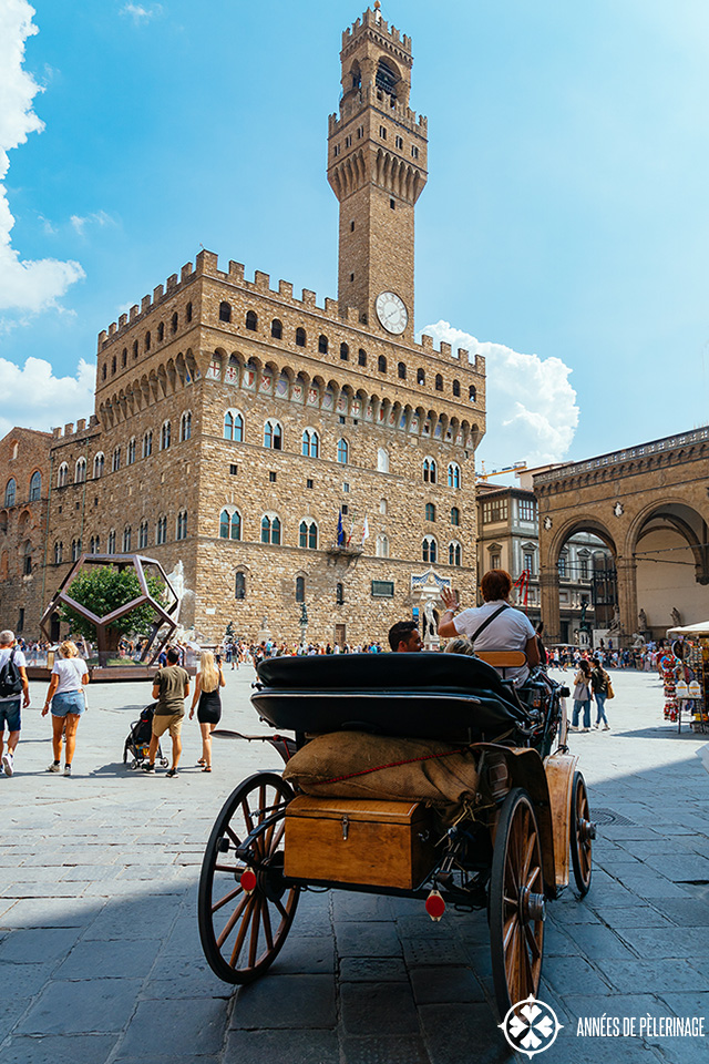 The Palazzo Vecchio in the center of Florence with a horse carriage in the forefront