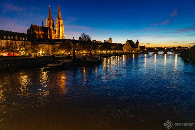 Regensburg, the old stone bridge, the river danube and the cathedral at night