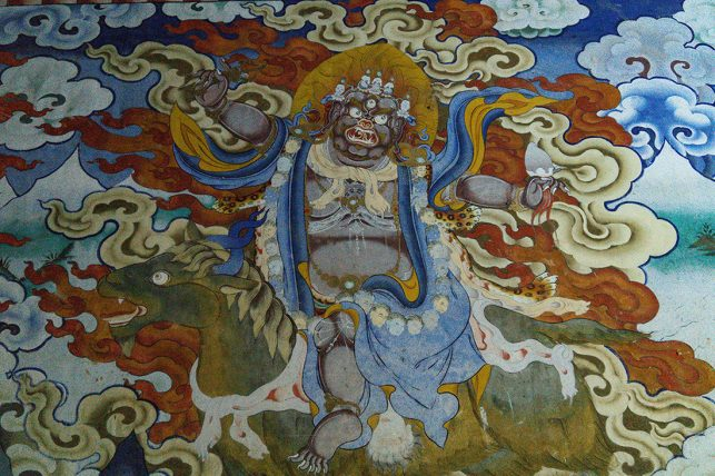 Guru Rinpoche (in his wrathful form) riding through the sky across Bhutan