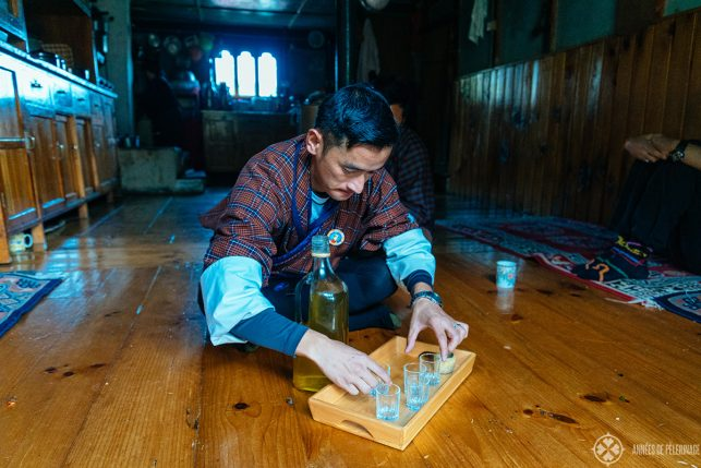 Our guide pouring some traditional schnaps in Bhutan