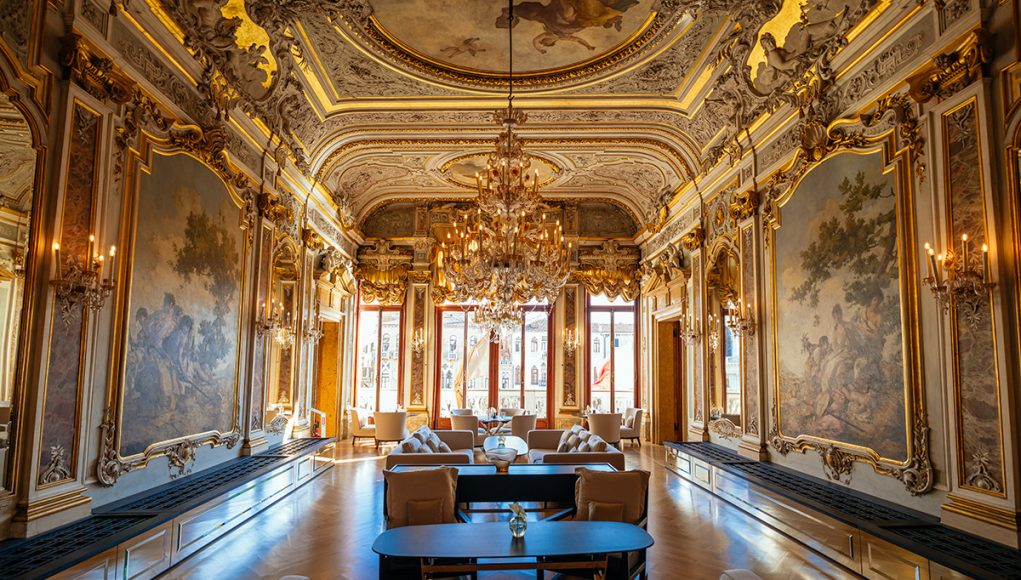 The main restaurant on the second floor of AMan Venice, with golden stucco work, chandeliers and frescos all over