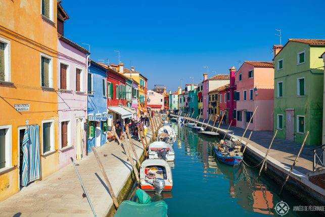 The picturesque main water channel on the island of Burano with many tiny colorful houses on each side of the water