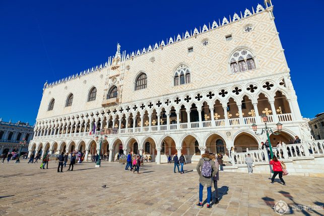 The facade of the Doge's Palace - all white marble. A tier of gothic arches with four leafed rosettas is topped by a larger tier in a pattern reminisicent of persian rugs