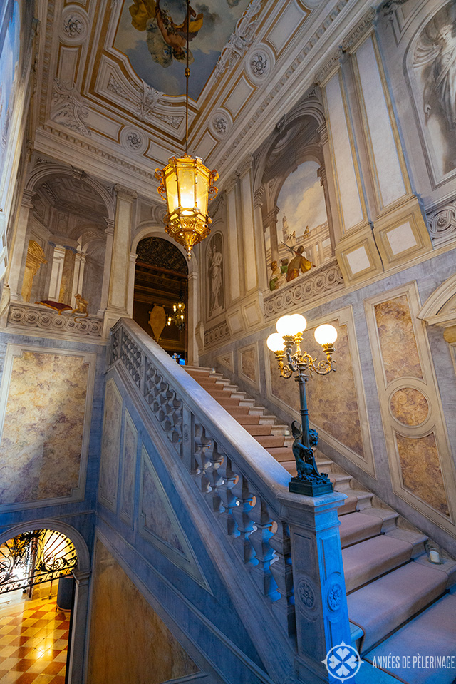 The main staircase of Aman Venice with beautiful frescoes lamps and marble inlays