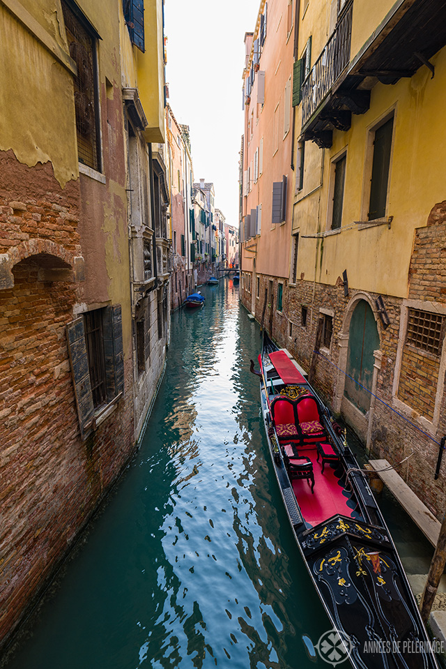 A couple of gondolas sitting in a narrow water way in Venice, Italy