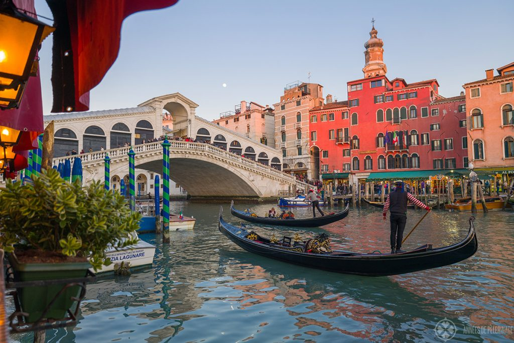 A gondola with a gondolier in a red-white striped shirt in front of the rialto bridge