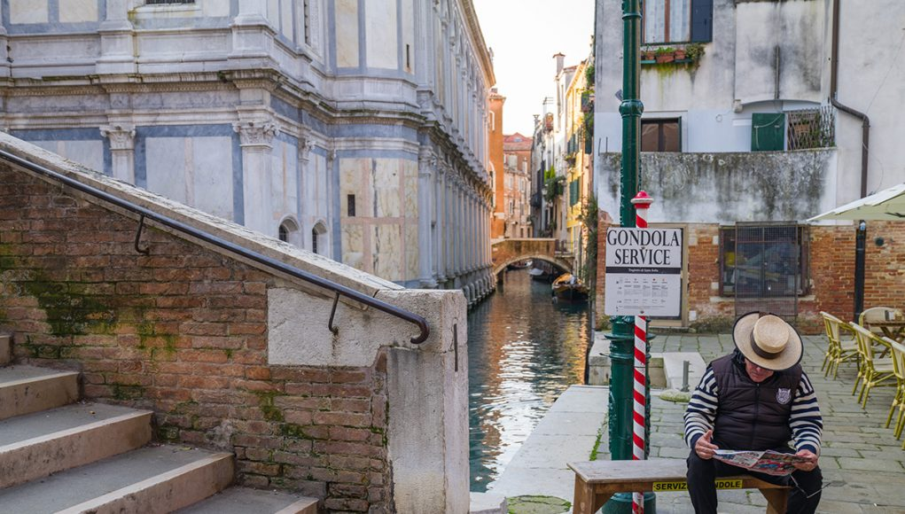 a gondolier waiting for customers in front of a sign saying